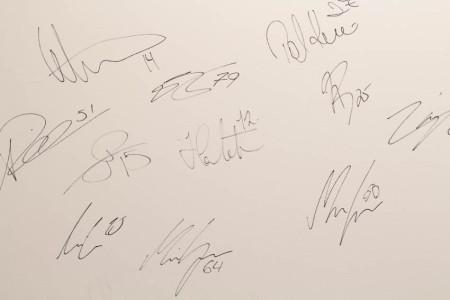 Suomalaisten huippukiekkoilijoiden nimikirjoituksia Idealfysion seinällä
